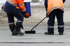 2 работника дороги в прозодеждах политы с горячей смолкой на краю прокладки дороги ремонтируя дорогу Стоковая Фотография RF