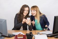 2 работника офиса восторженно обсуждая что-то на мобильном телефоне на его столе Стоковая Фотография