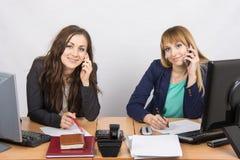 2 работника офиса говоря на мобильном телефоне на его столе Стоковая Фотография RF
