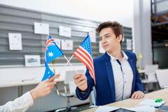 2 работника офиса держат 2 флага Америки и Австралии Внутри офиса Стоковые Изображения RF