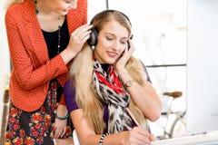 2 работника офиса на столе слушая к музыке Стоковое фото RF
