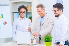 3 работника офиса обсуждая проект Стоковые Фотографии RF