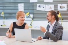 2 работника офиса сидят на компьтер-книжке и обсуждают что-то Стоковое фото RF