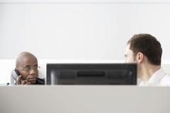 2 работника офиса сидя в кабине офиса Стоковые Фото