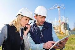 2 работника работая снаружи с таблеткой на строительной площадке Стоковые Изображения