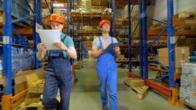 2 работника склада сравнивают размещение хранения с их напечатанными планами акции видеоматериалы