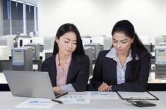 2 работника смотря диаграмму на столе Стоковые Изображения RF