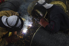 2 работника совместно сваривая большую трубку для топления города Стоковое фото RF