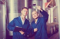 2 работника с образцом вина на винодельне Стоковое фото RF