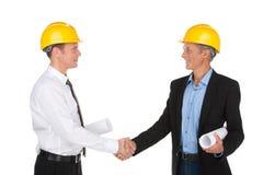 2 работника тряся руки и усмехаться. Стоковые Изображения RF