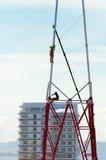 2 работника устанавливают много башню металла tiered. Стоковая Фотография