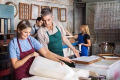 Работники анализируя бумаги в фабрике стоковая фотография