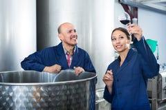 Работники винодельни держа стеклянными в фабрике вина Стоковые Фото