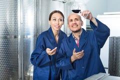 Работники винодельни держа стеклянными в фабрике вина Стоковое Фото