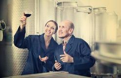 Работники винодельни держа стеклянными в фабрике вина Стоковое фото RF