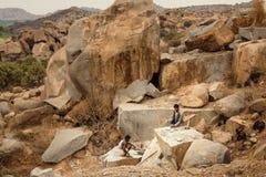 Работники вручную копая камень экскаватором на открытой шахте Стоковое Изображение RF