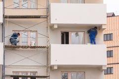 Работники выполняют отделку и картину фасад многоэтажных зданий Стоковые Фото