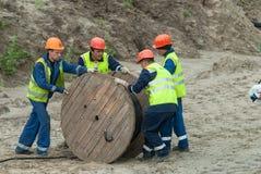 Работники вытягивая кабельную линию связи высокого напряжения крена Стоковые Фотографии RF