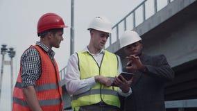 Работники в жилетах показывая боссу что-то на таблетке сток-видео