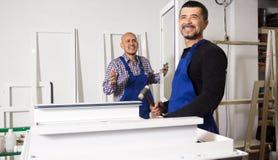 работники в мастерской собирают конструкцию PVC Стоковое фото RF