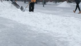 Работники в оранжевых куртках с лопаткоулавливателями и трактором снегоочистителя очищают улицу после пурги Муниципальный городск сток-видео