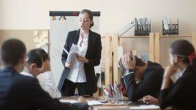 Работники деловой компании сидят держащ их головы после бедно выполненной работы, пока они подверганы наказанию  акции видеоматериалы