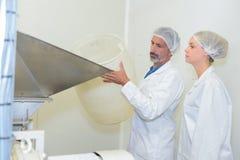 Работники добавляя материал в фабрике стоковые изображения rf