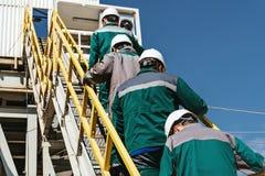 Работники идут к буровой вышке стоковые фотографии rf