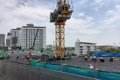 Работники изготовляя форма-опалубку тимберса столбца и бар подкрепления на строительной площадке Стоковое Фото