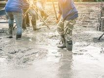 Работники используя деревянный шпатель для цемента после лить готов-смешанный бетон стоковое фото rf