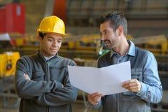Работники и менеджер на фабрике стоковые фото