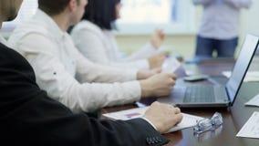 Работники компании сидя на таблице в деловой встрече, слушая к речи вождей акции видеоматериалы