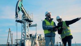 Работники месторождения нефти обсуждая проект, стоя на поле, конец вверх видеоматериал