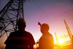 работники наблюдая башню и подстанцию силы с заходом солнца b Стоковые Изображения RF