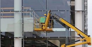 Работники на автотелескопической вышке Они заканчивают стеклянный фасад здания под реновацией стоковая фотография rf