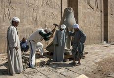 Работники на виске Horus на Edfu в Египте делая новое основание для одного из соколов на входе опоры Стоковое Изображение RF