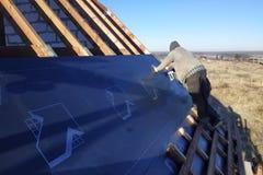 Работники на крыше дома устанавливают водоустойчивый фильм под крышу и обеспечивают ее со сшивателем стоковое изображение rf