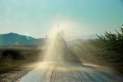 Работники на тележке воды распыляют воду на дороге для того чтобы держать пыль вне Стоковое Изображение
