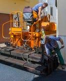 Работники на управлении машины paver чертить стоковое изображение