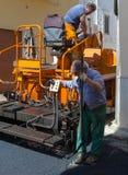 Работники на управлении машины paver чертить стоковые фото