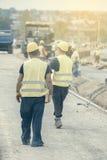 Работники нося тяжелую деревянную планку 2 Стоковые Фото