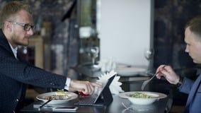 Работники обсуждая проект при таблетка есть в кафе во время дела сток-видео