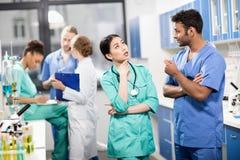 Работники обсуждая работу с коллегами позади в лаборатории Стоковые Изображения RF