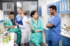 Работники обсуждая работу с коллегами позади в лаборатории Стоковое Фото