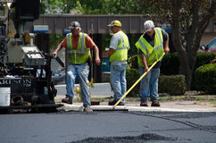 Работники дороги сгребая горячий асфальт Стоковое Изображение