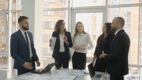 Работники офиса, работники большой компании, 2 молодого человека и 3 молодой женщины стоя около таблицы с документами сток-видео