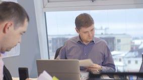 Работники офиса взгляда со стороны смотрят через бумаги на компьтер-книжке