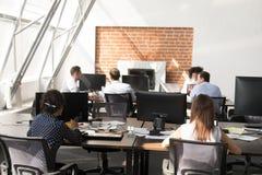 Работники офиса используя компьютеры работая на современном большом открытом пространстве стоковая фотография rf