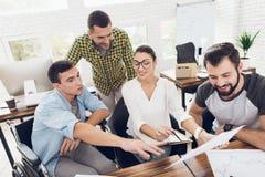 Работники офиса и персона в кресло-коляске обсуждают работать дела Они работают в ярком офисе Стоковые Фотографии RF