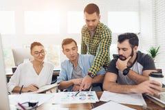 Работники офиса и персона в кресло-коляске обсуждают работать дела Они работают в ярком офисе Стоковая Фотография